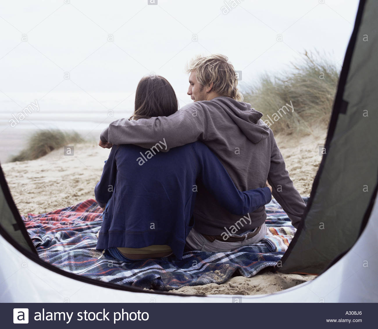 Couple sitting outside tent - Stock Image