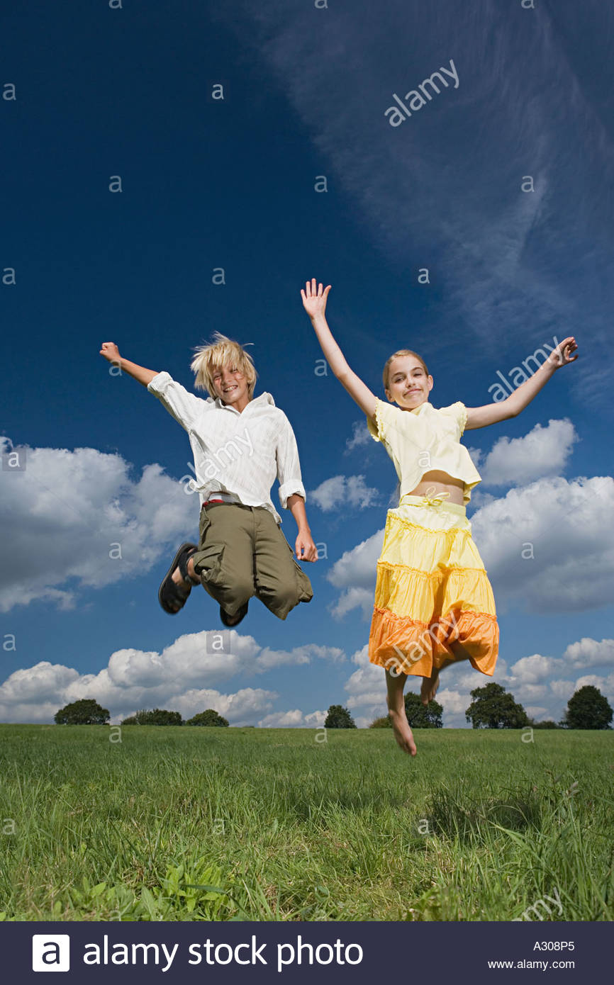 Children jumping in a field - Stock Image