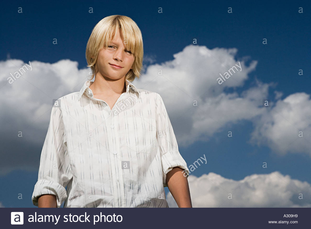 Boy in front of a cloudy sky - Stock Image
