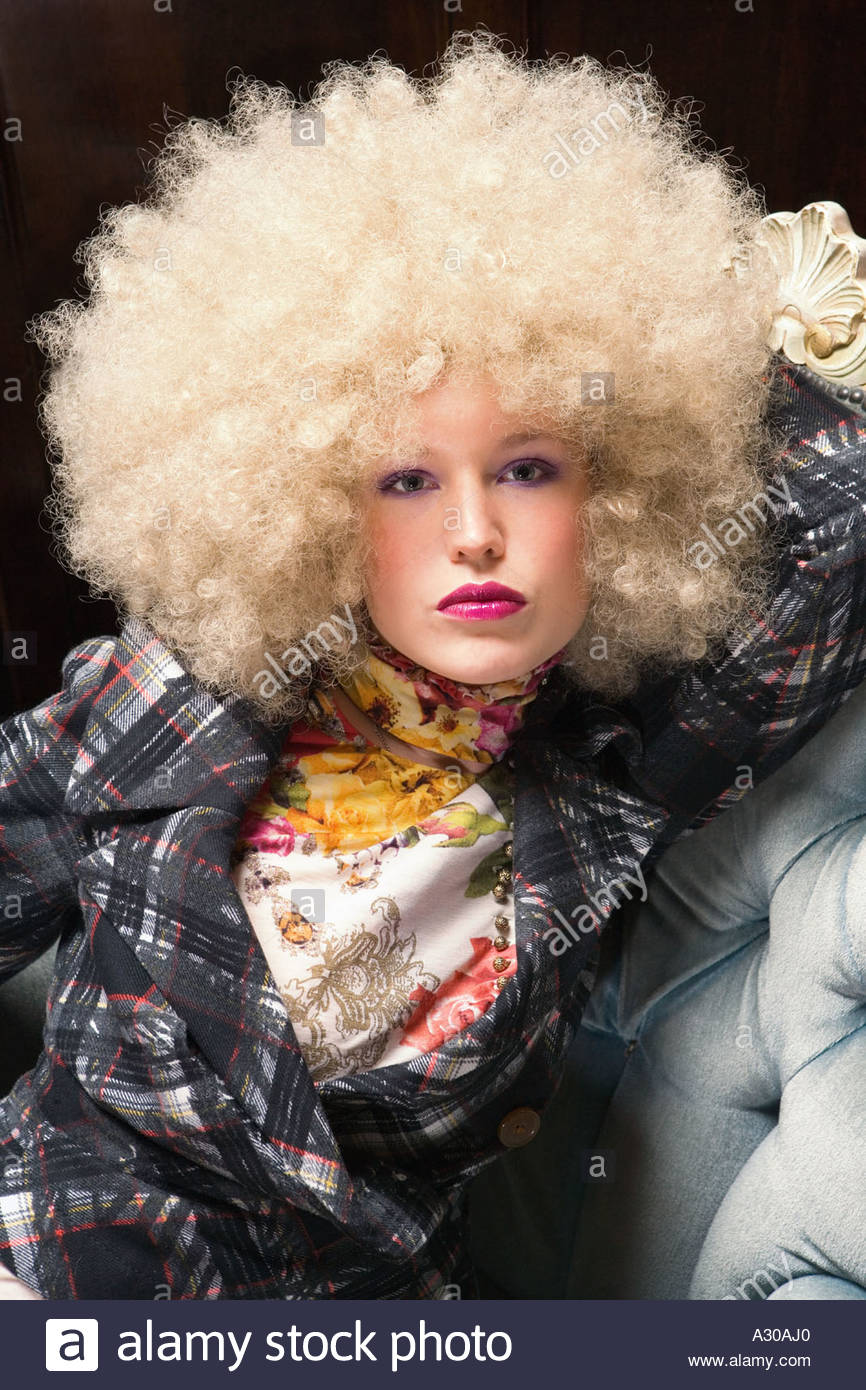 Woman wearing blond afro wig Stock Photo