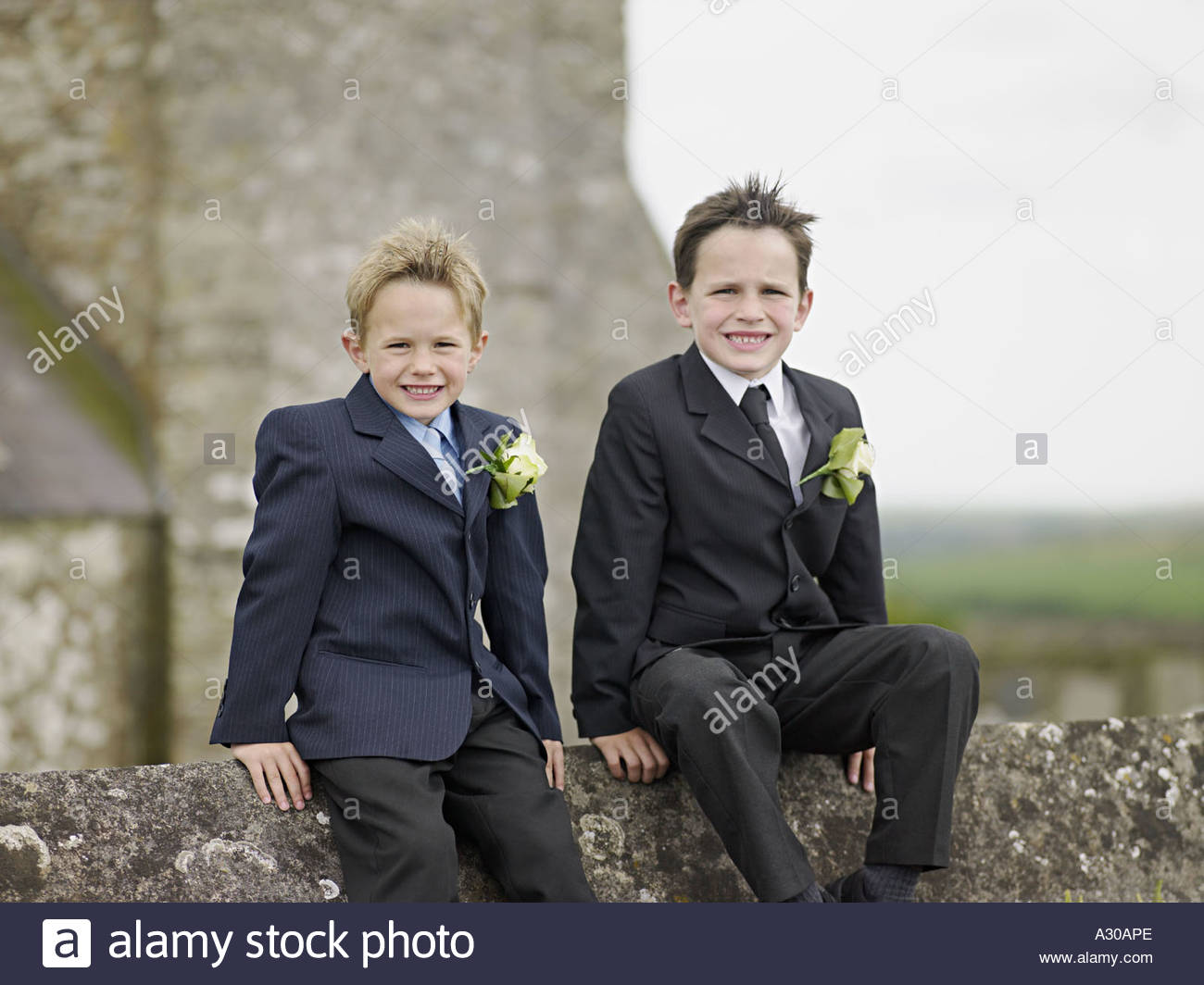 Two boys on wall outside church - Stock Image