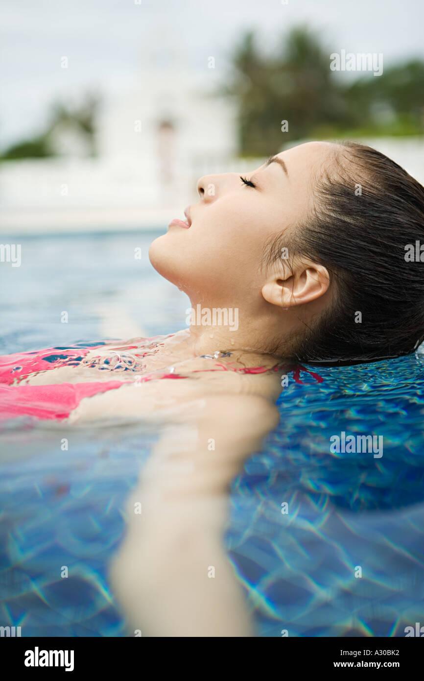 Beautiful woman relaxing in swimming pool - Stock Image