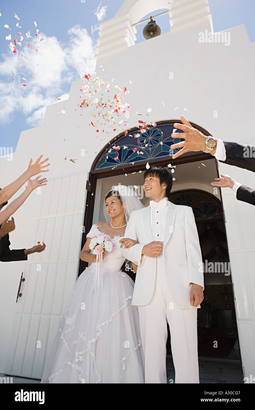 Guests throwing confetti over newlyweds Stock Photo