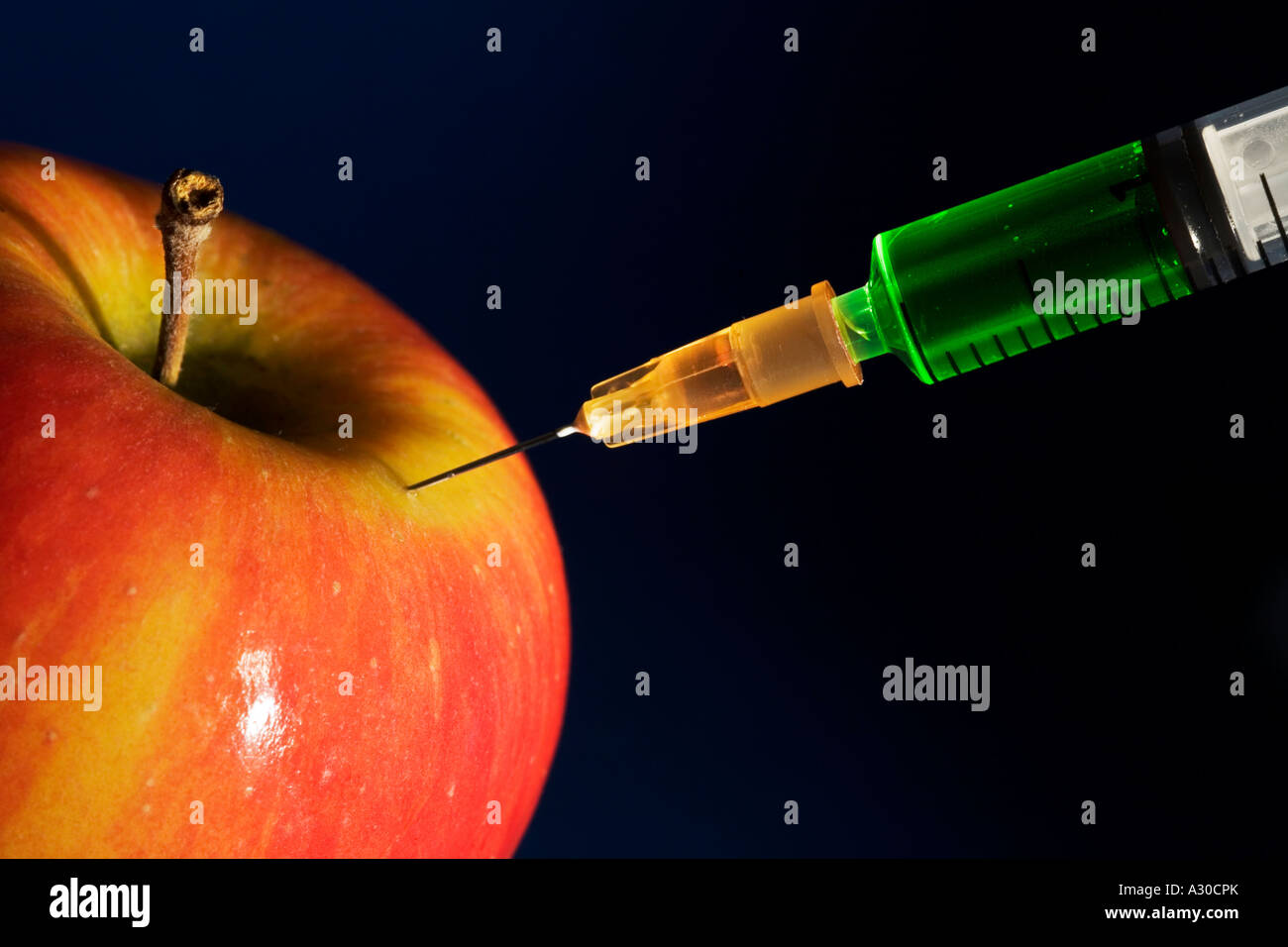 Apple injected with green liquid Concept to represent genetically modified food - Stock Image