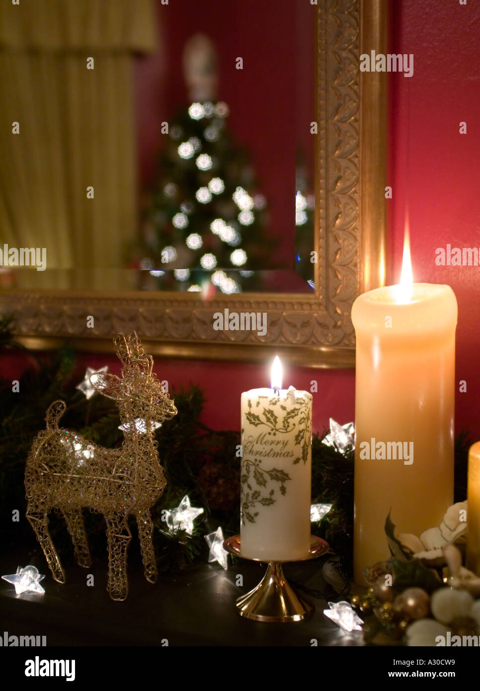 christmas candles and decorations on mantelpiece with christmas tree reflected in gold framed mirror stock