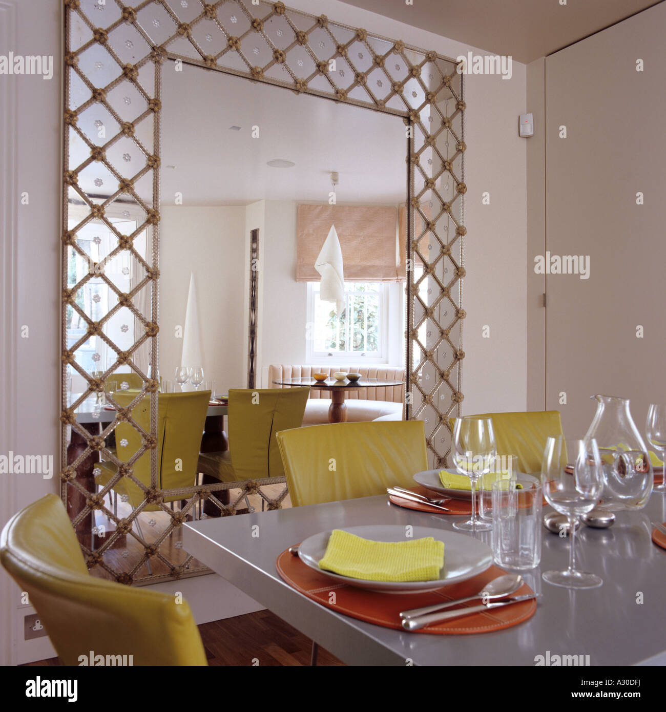 Oversized Mirror With Fretwork In Dining Room With Table And Yellow Stock Photo Alamy