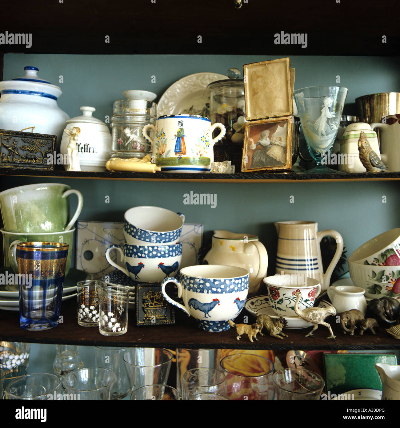 Assortment of crockery and cups on shelf in country kitchen - Stock Image