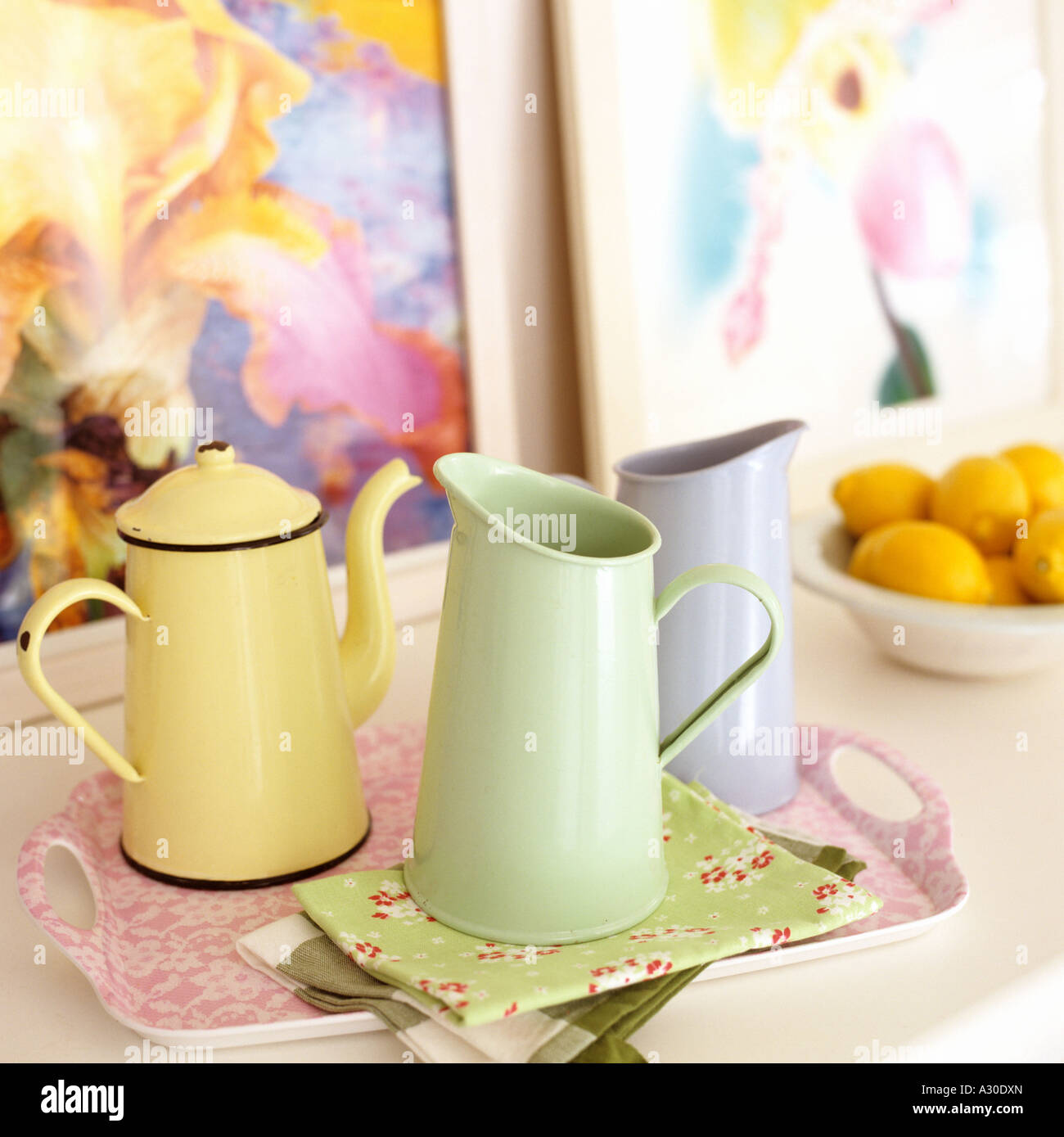 Display of coloured retro enamel and ceramics jugs on floral napkins - Stock Image
