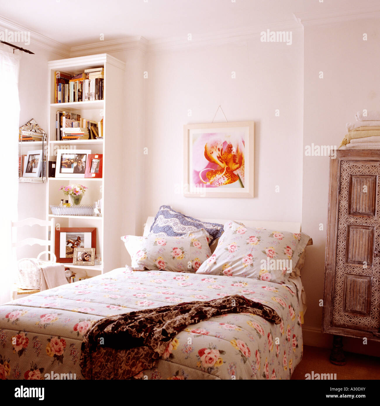 Floral patterned bed cover on queen sized bed under artwork with bookcase - Stock Image