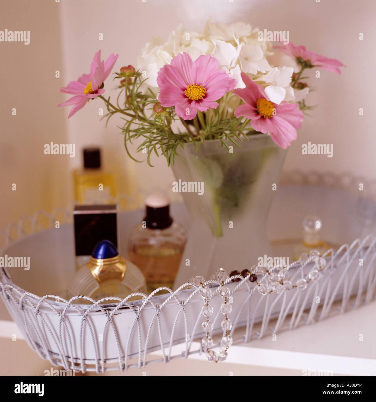 Flower arrangement and perfume bottles on metalwork tray - Stock Image