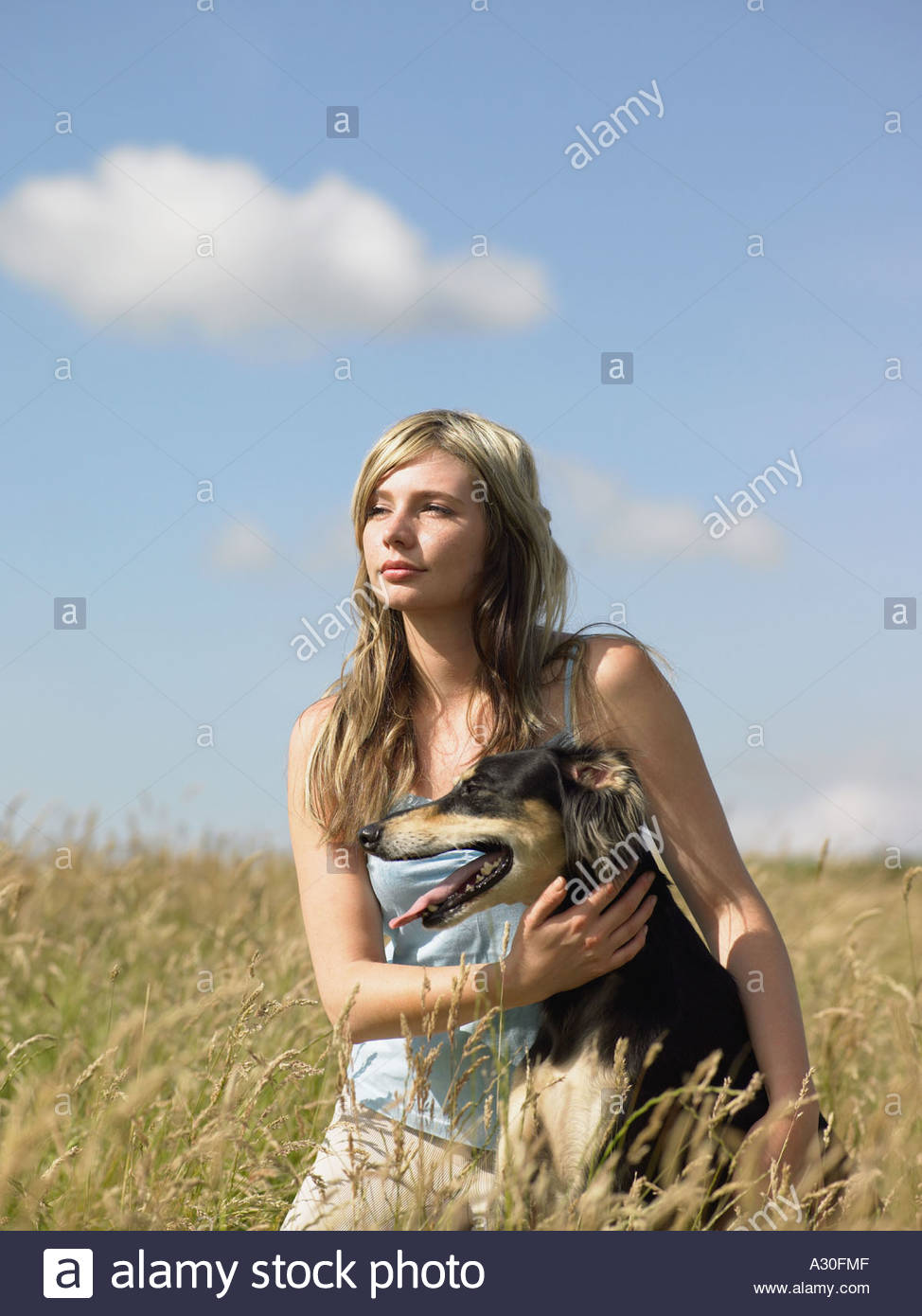 Young woman with dog in field - Stock Image
