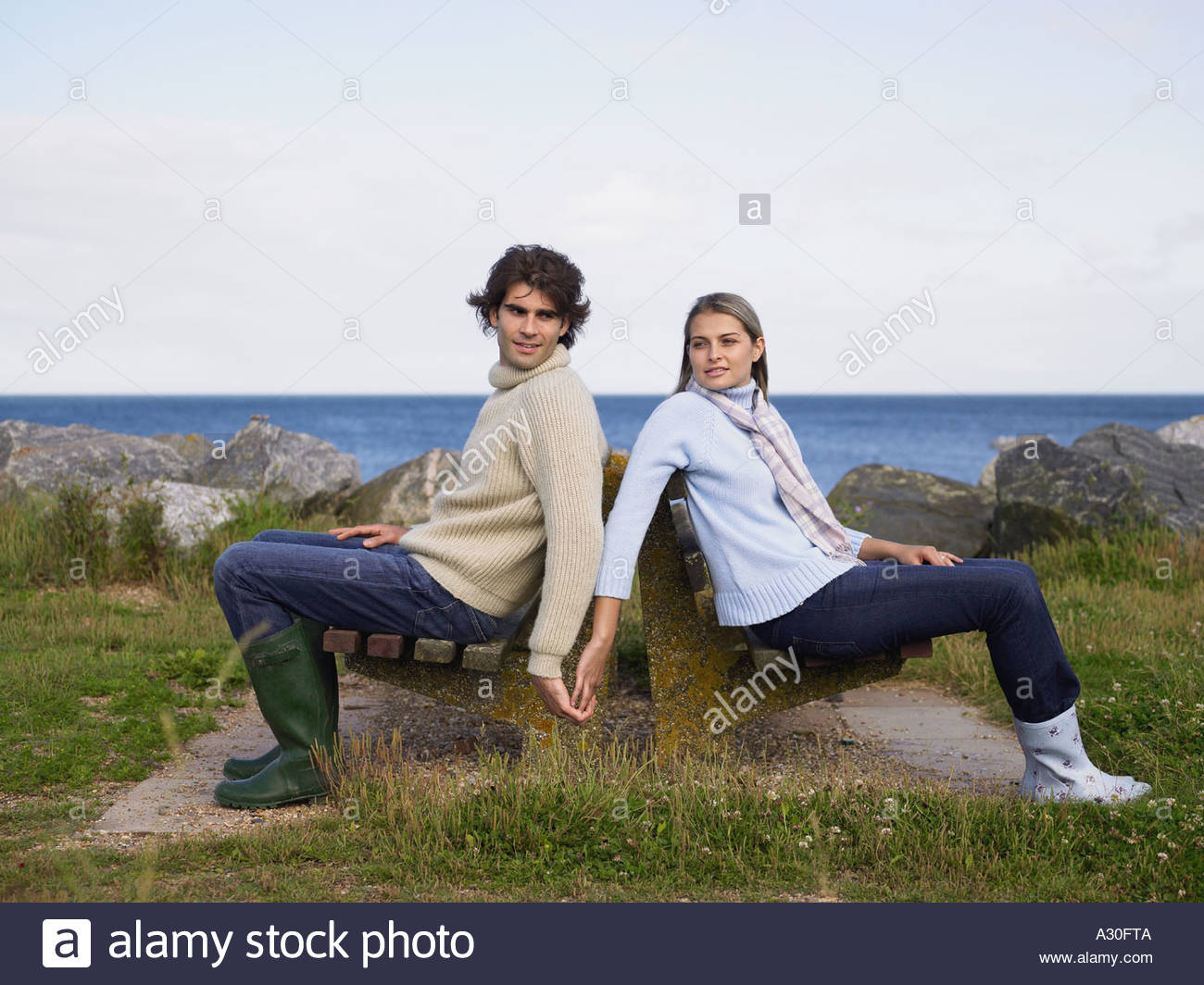 Couple on bench by ocean - Stock Image