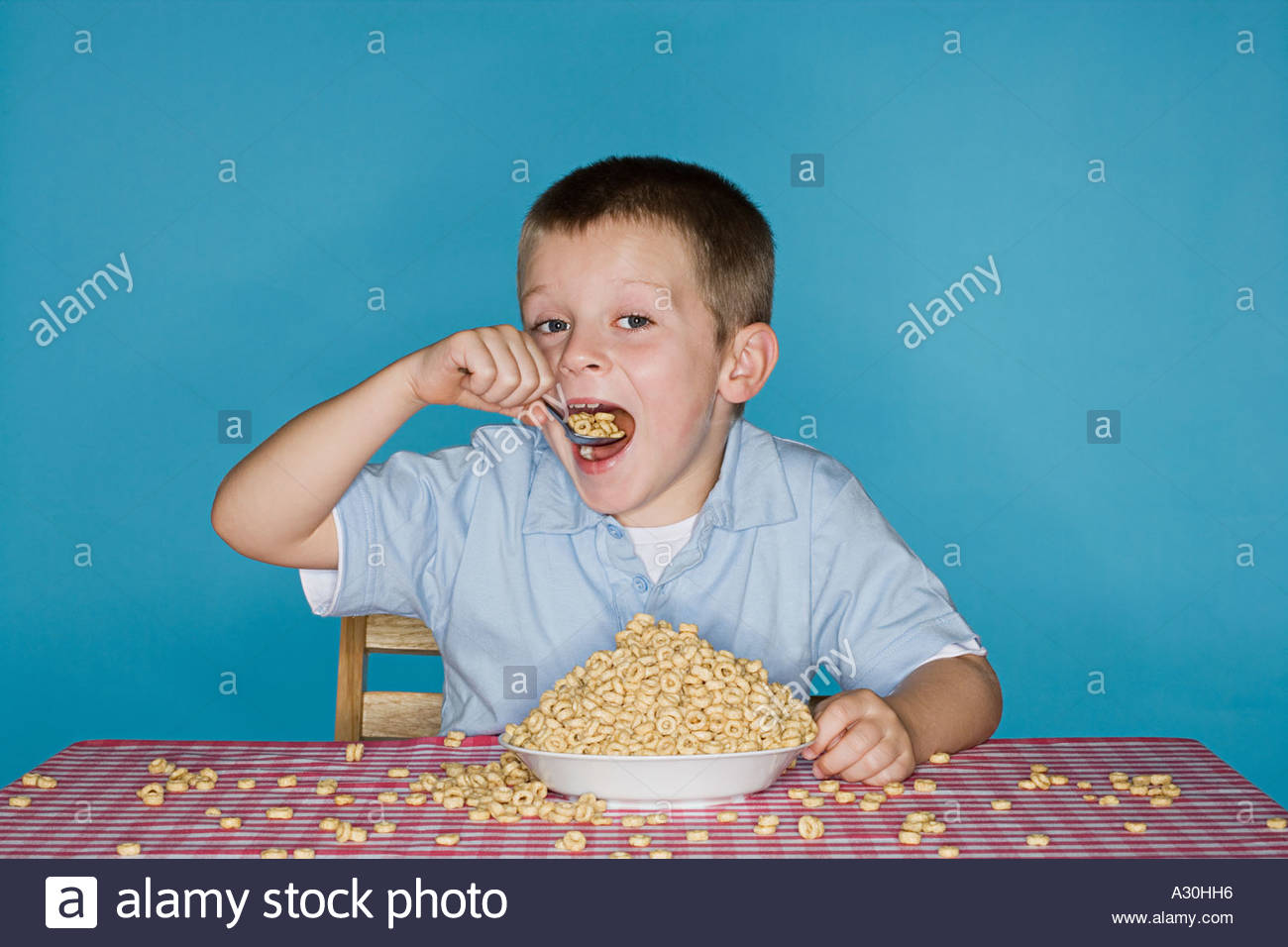 Boy with lots of breakfast cereal - Stock Image