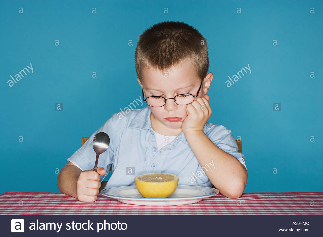 Sullen boy with grapefruit - Stock Image
