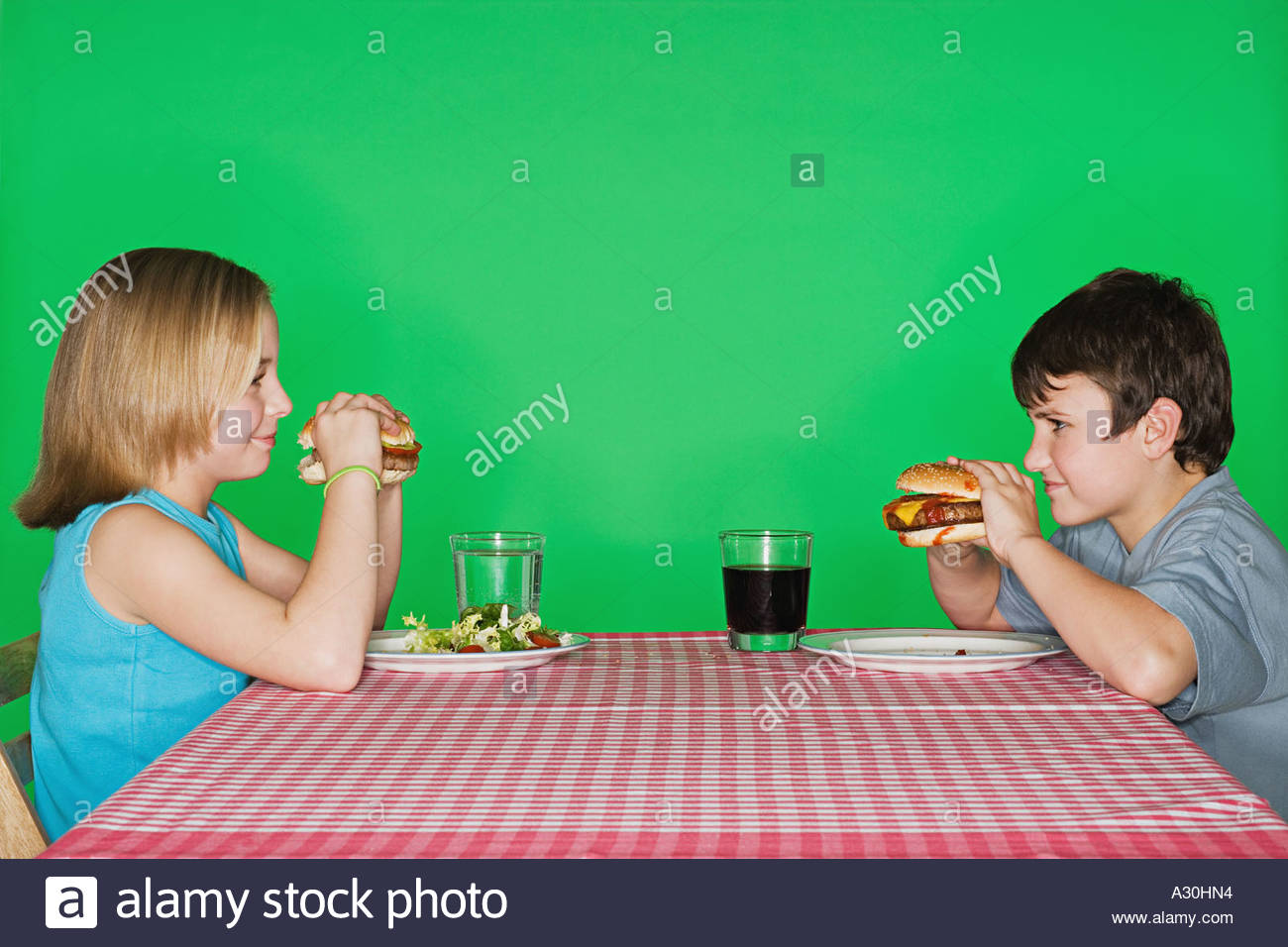 Girl and boy eating burgers - Stock Image