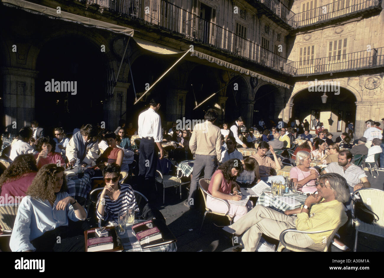 people sitting at tables chairs in crowded outdoor cafe salamanca piazza - Stock Image