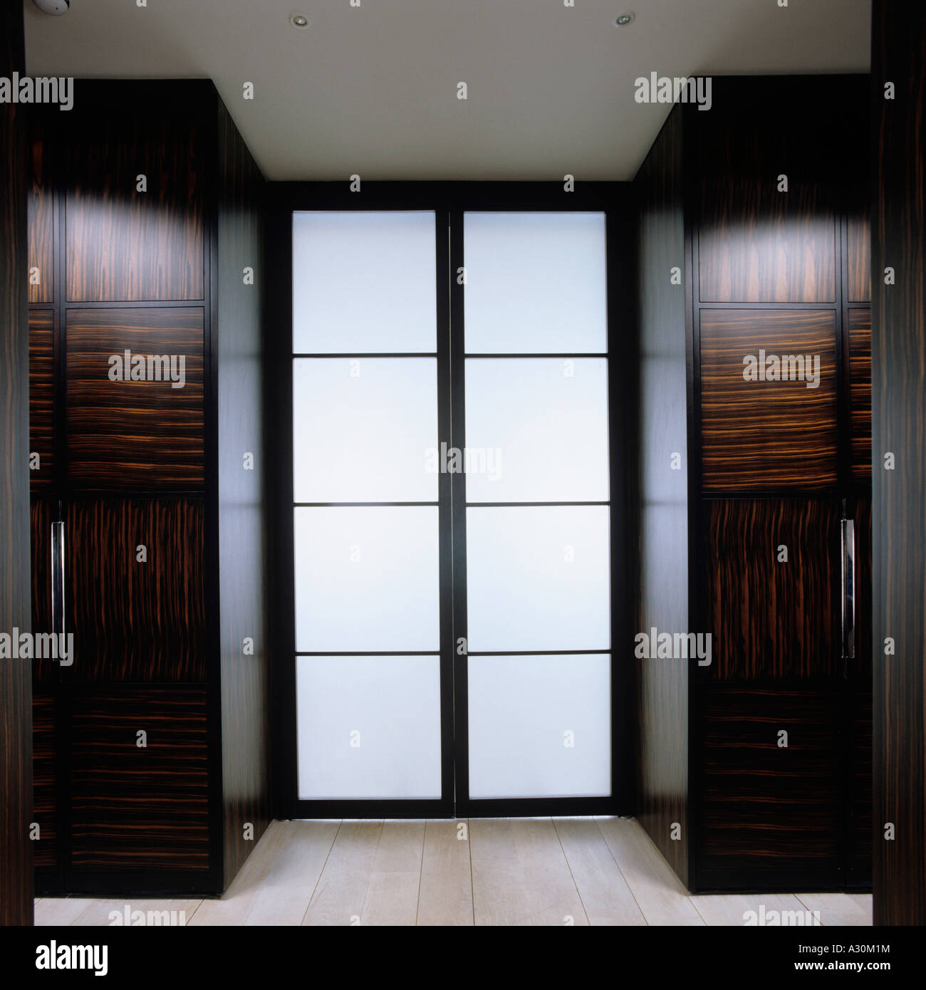 Glass double door with two polished walnut wardrobes - Stock Image