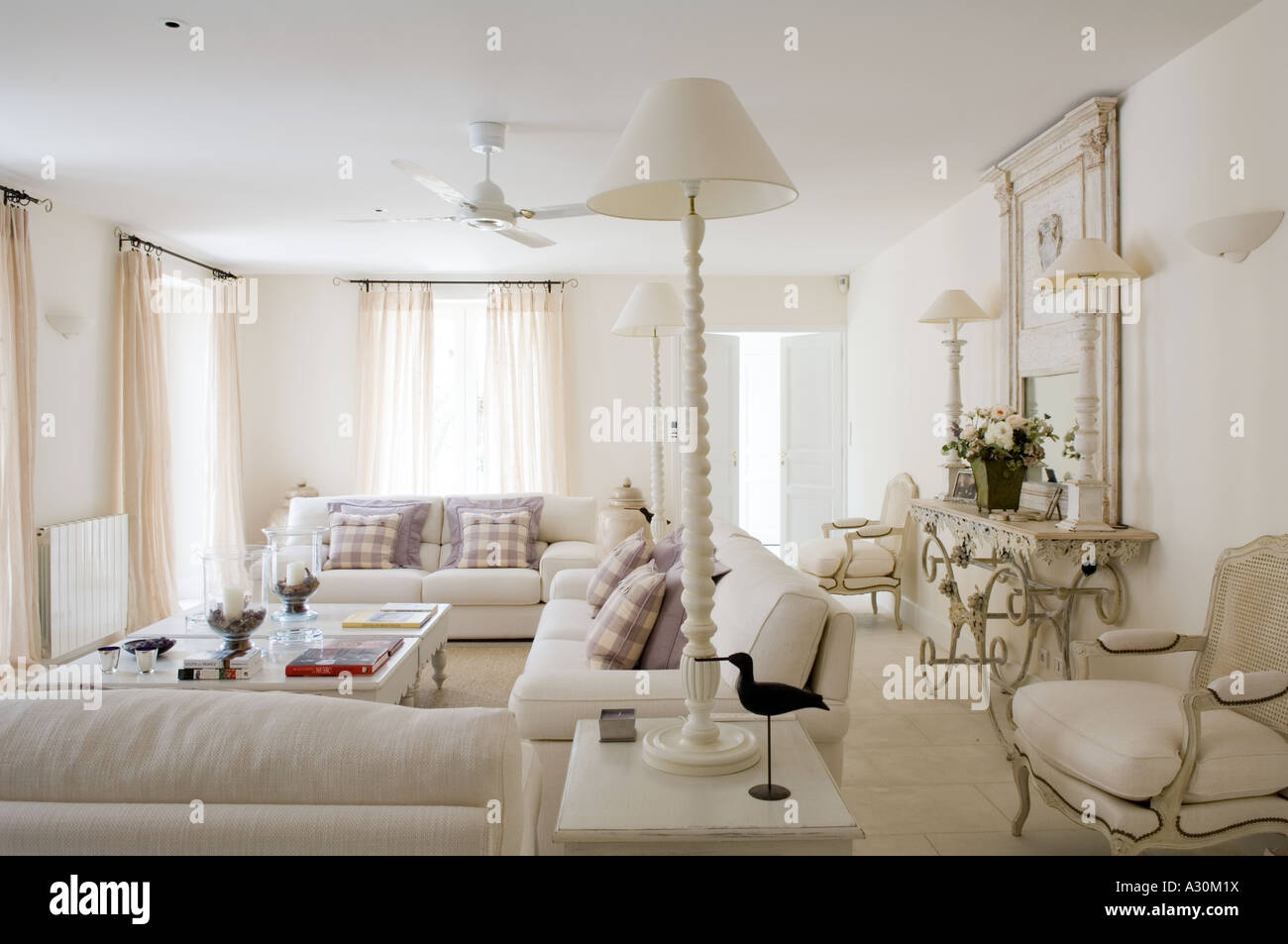 White living room with matching lamps and ceiling fan Stock Photo ...