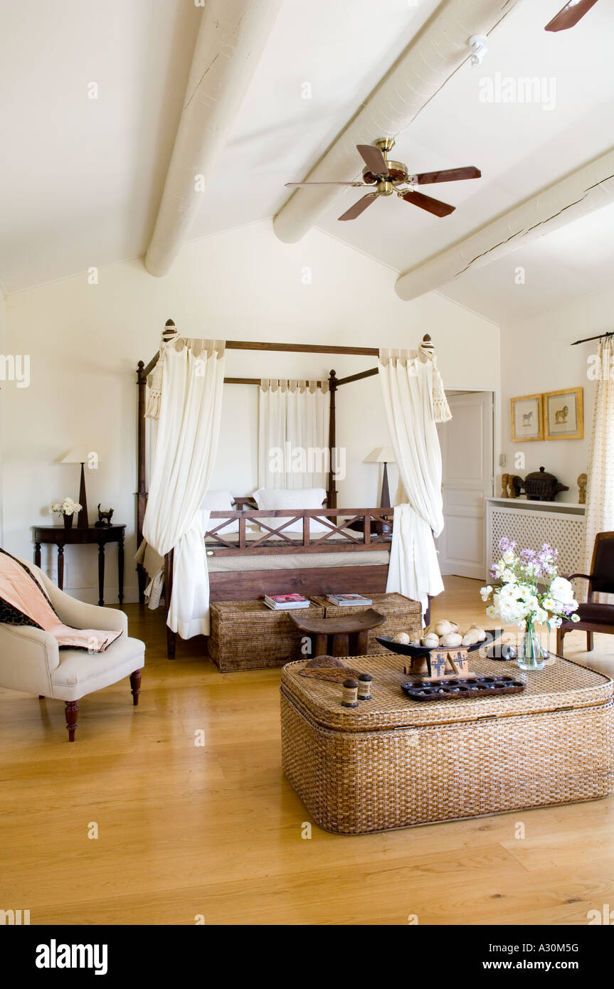 Bedroom with wicker storage chest, four poster bed and ceiling fan - Stock Image