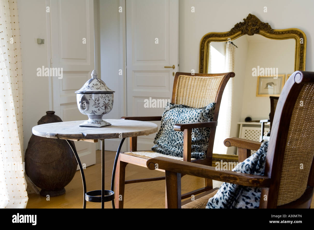 Two wicker chairs at a side table with a gilt framed mirror - Stock Image