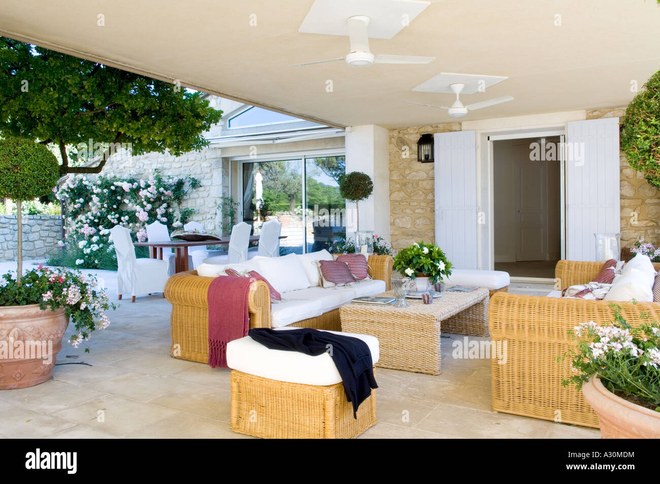 Terrace exterior with wicker furniture and ceiling fans - Stock Image