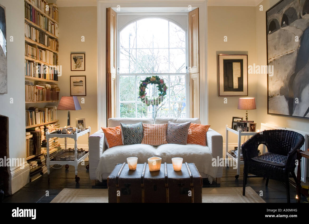 sofa underneath window with christmas wreath in the sitting room of a Georgian townhouse - Stock Image