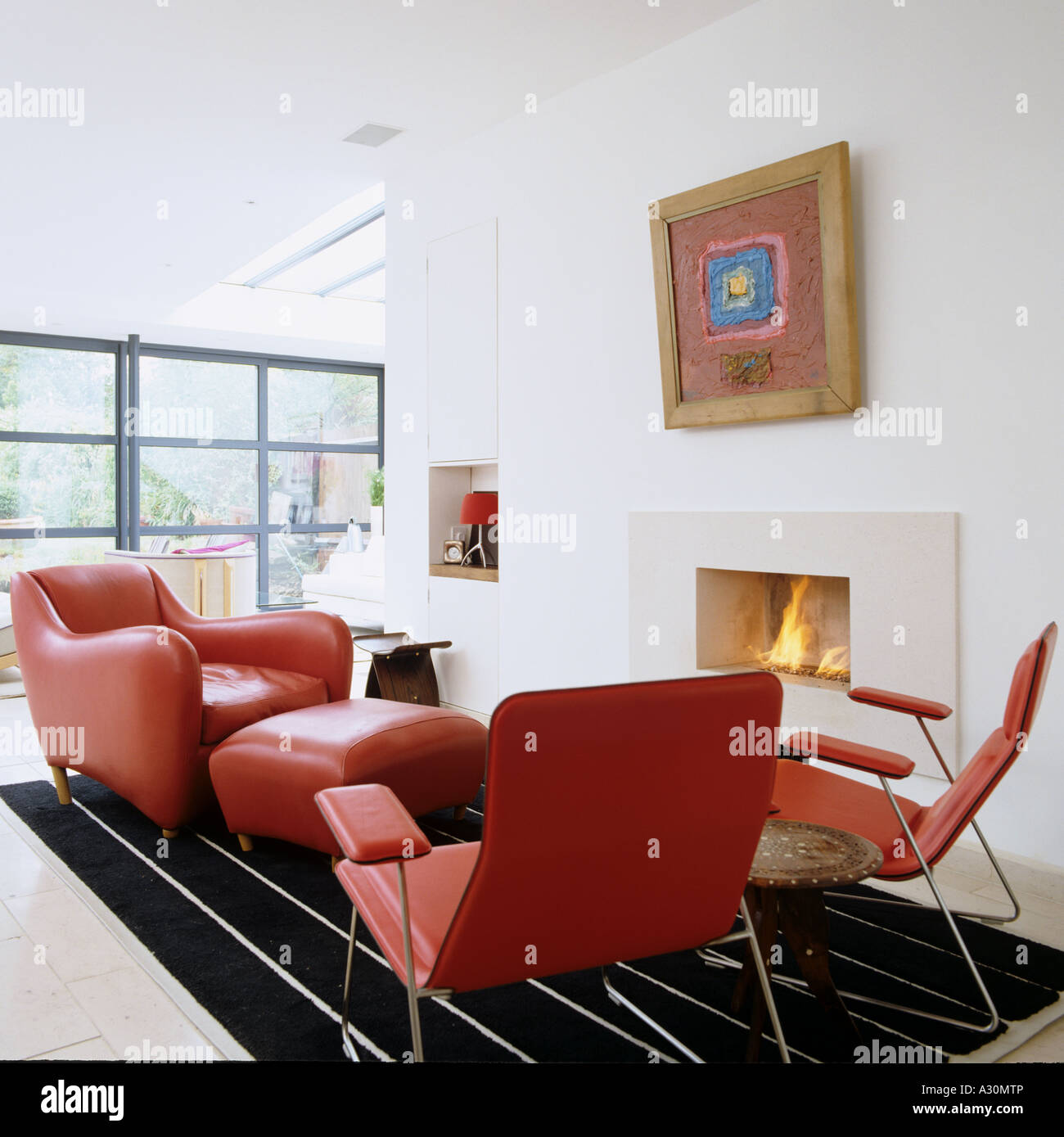 Modern Red Leather Furniture By Fireplace In Open Plan Living Room   Stock  Image
