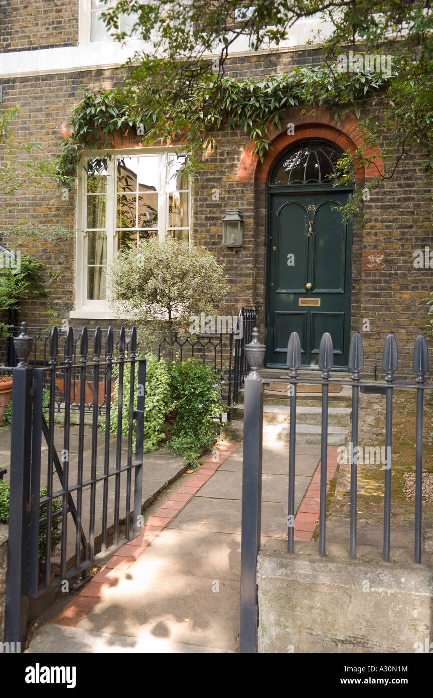 Open gate leading to green front door of London townhouse - Stock Image