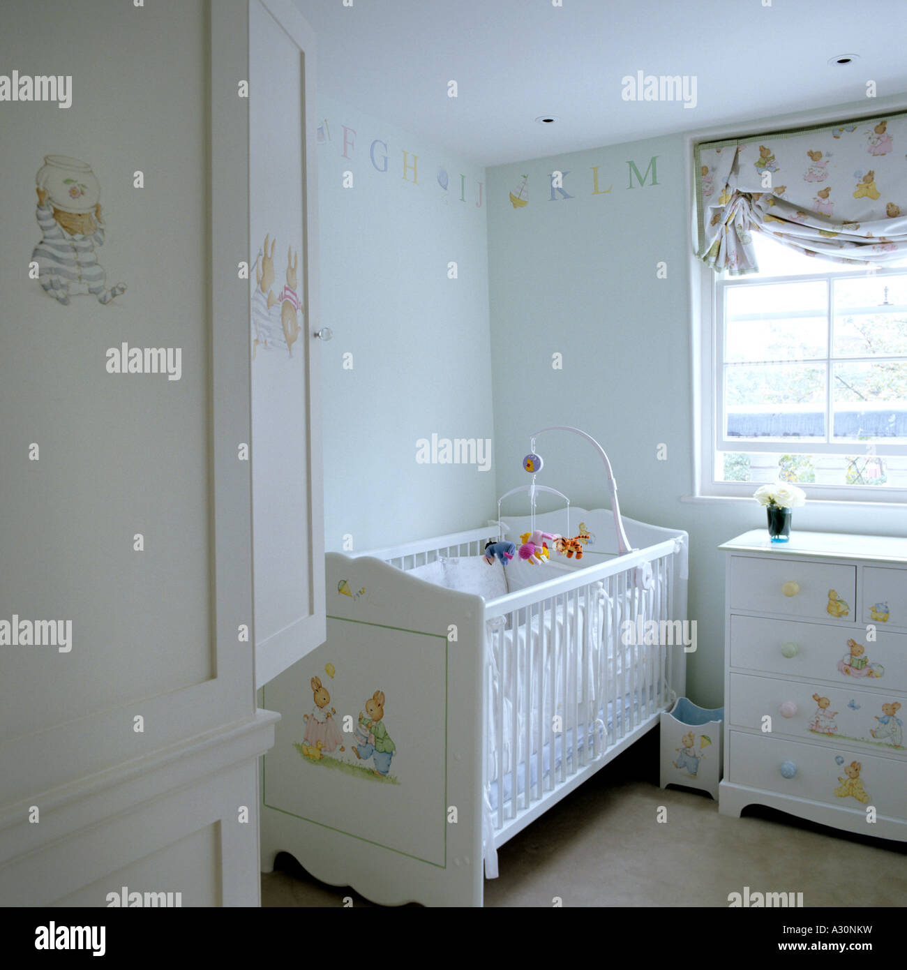 Cot in a child's nursery with Beatrix potter decoration - Stock Image