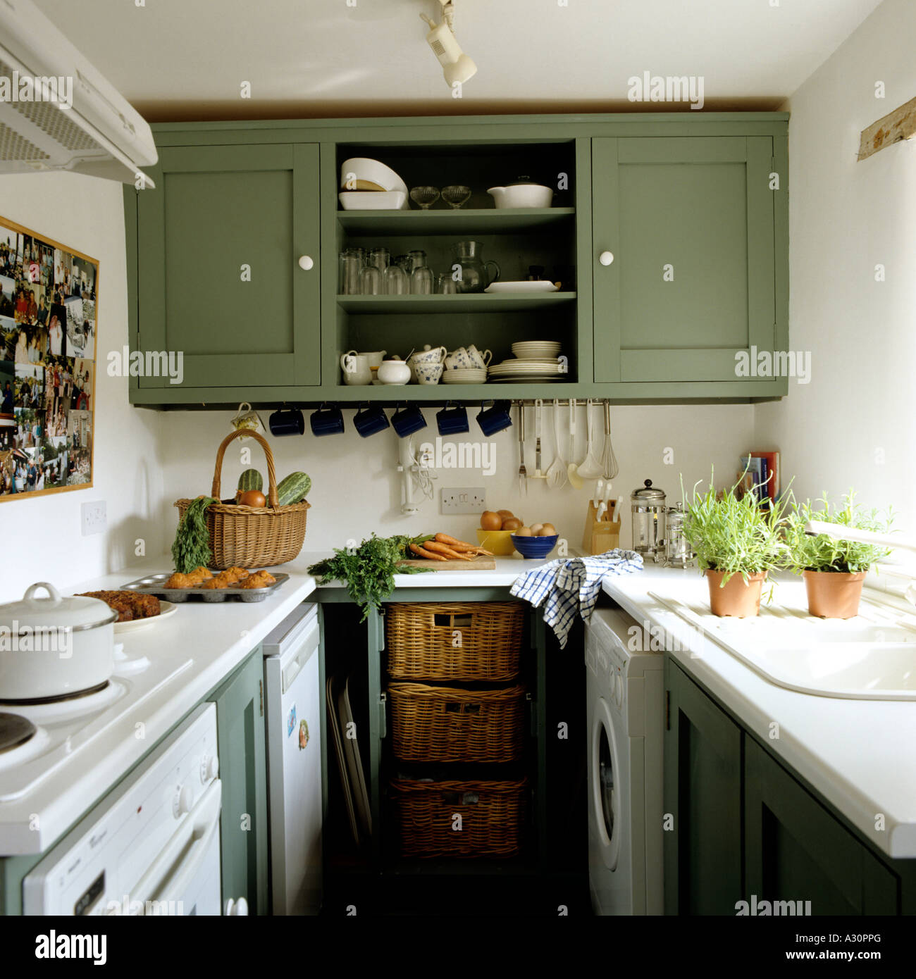 Green painted cupboard in galley kitchen, in English country cottage - Stock Image