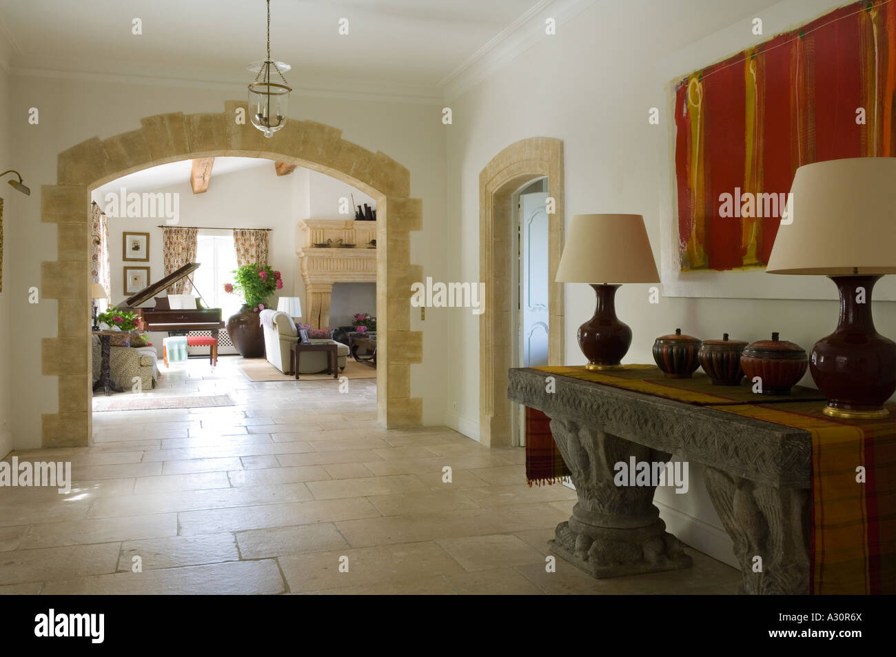 Console table with matching lamps in spacious limestone hallway - Stock Image