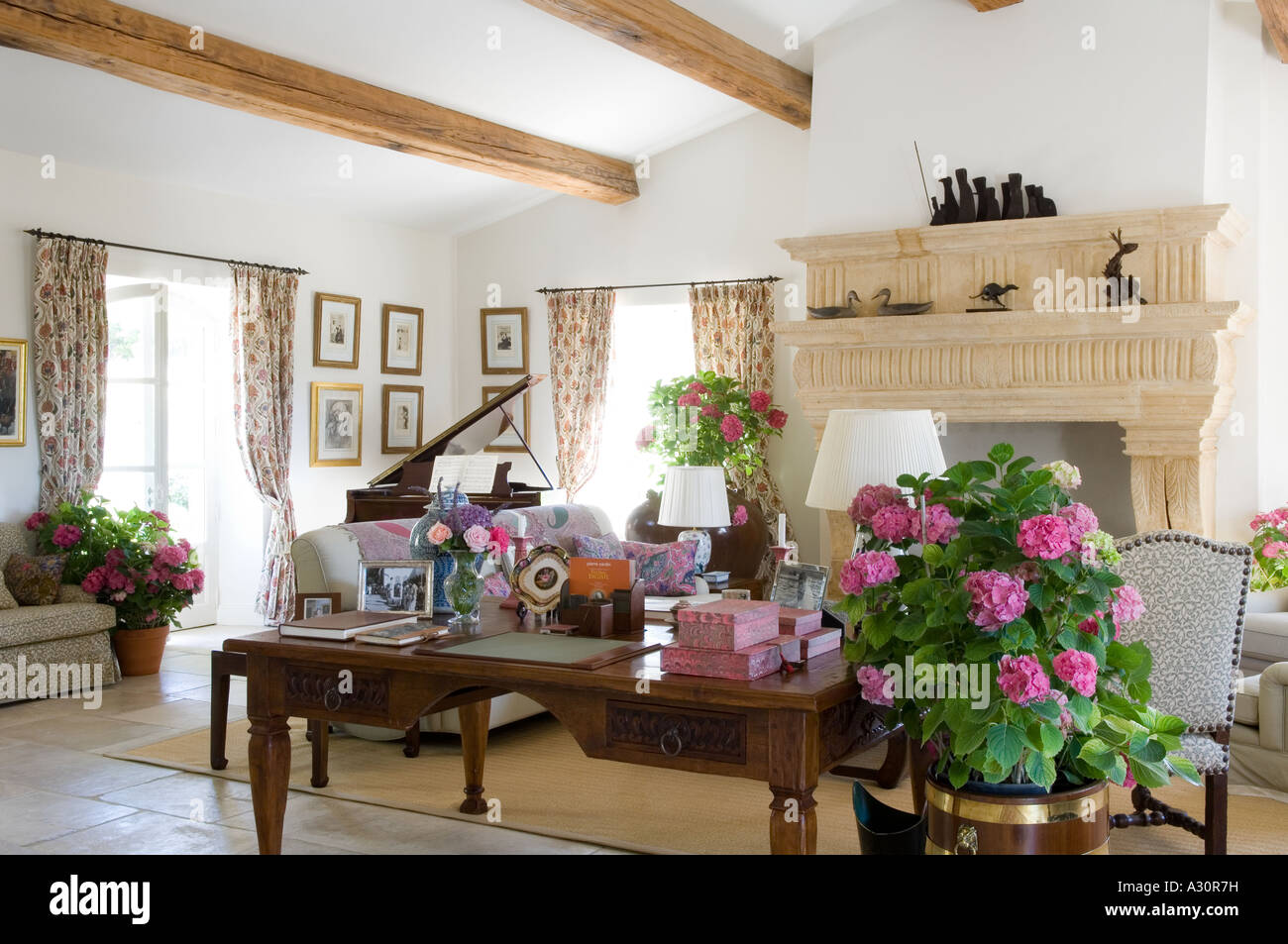 Houseplant and desk in beamed living room with stone fireplace Stock Photo