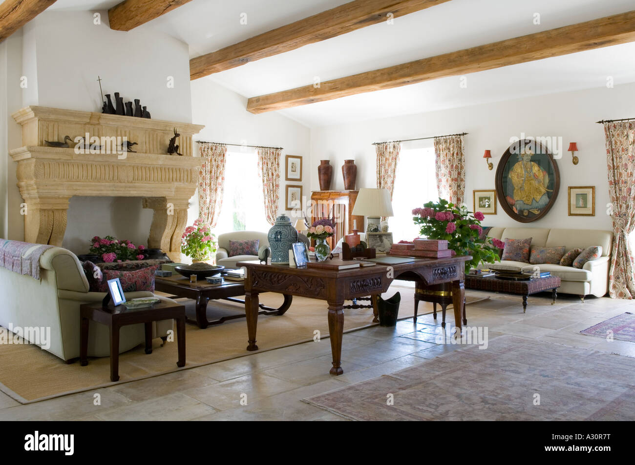 Spacious beamed living room with desk and stone fireplace - Stock Image