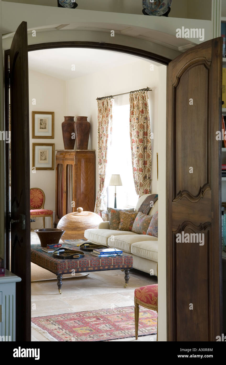 View through double doors to living room with ottoman - Stock Image
