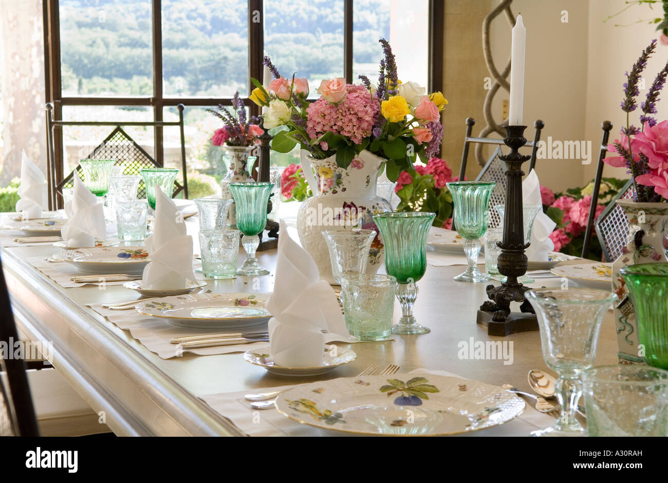 Table set with flower arrangements, wineglasses and napkins - Stock Image