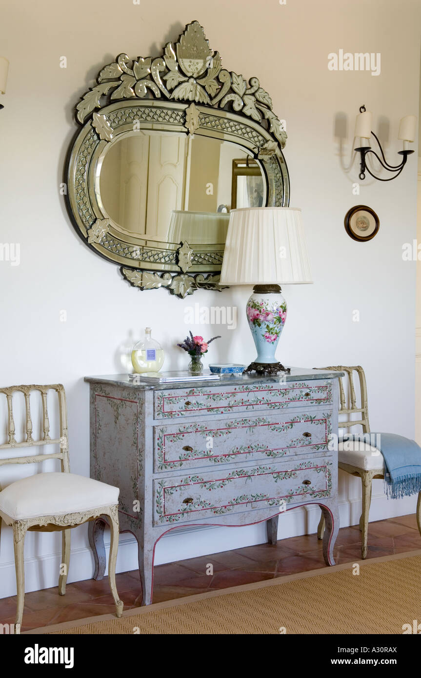 A decorated chest of drawers and a large mirror in a Provençal house - Stock Image