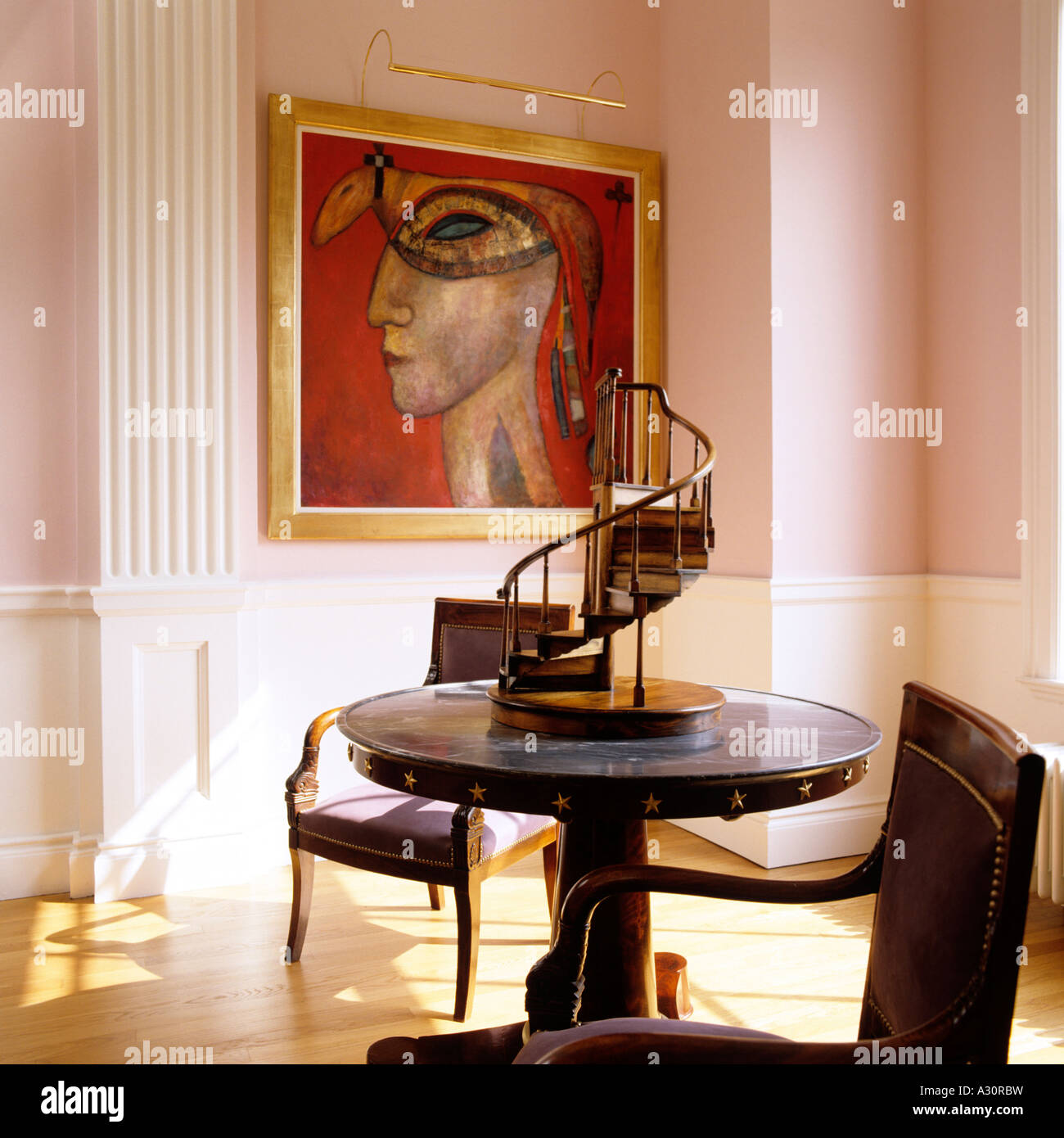 Wooden chairs at circular table with spiral step sculpture and surrealist  artwork - Stock Image