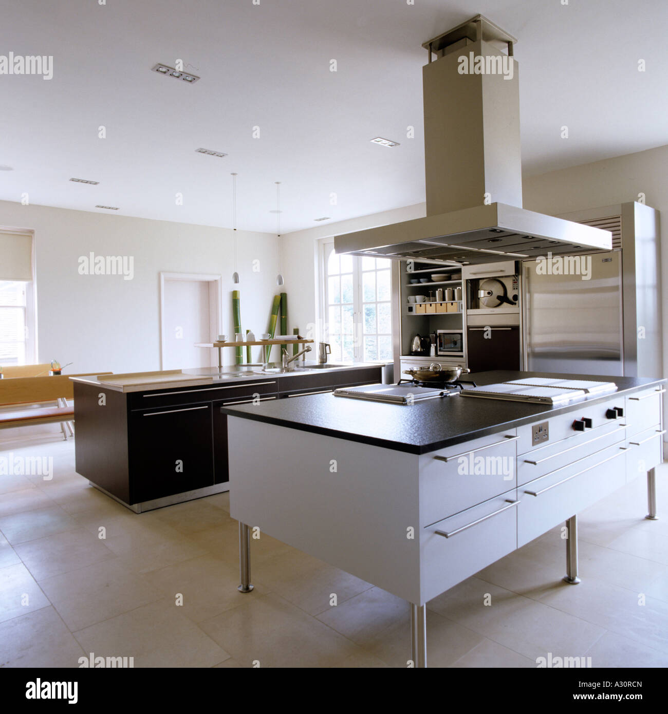 Modern kitchen with island and large extractor fan Stock Photo ...