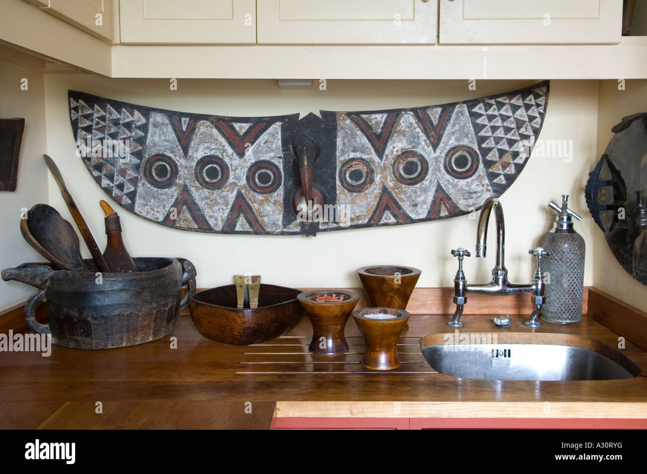 Kitchen sink area with African art - Stock Image