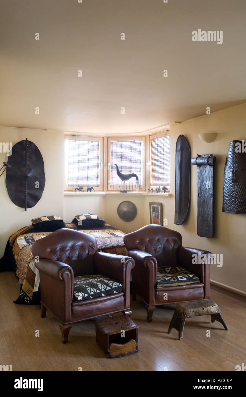 Bedroom with two leather armchairs and African artefacts - Stock Image