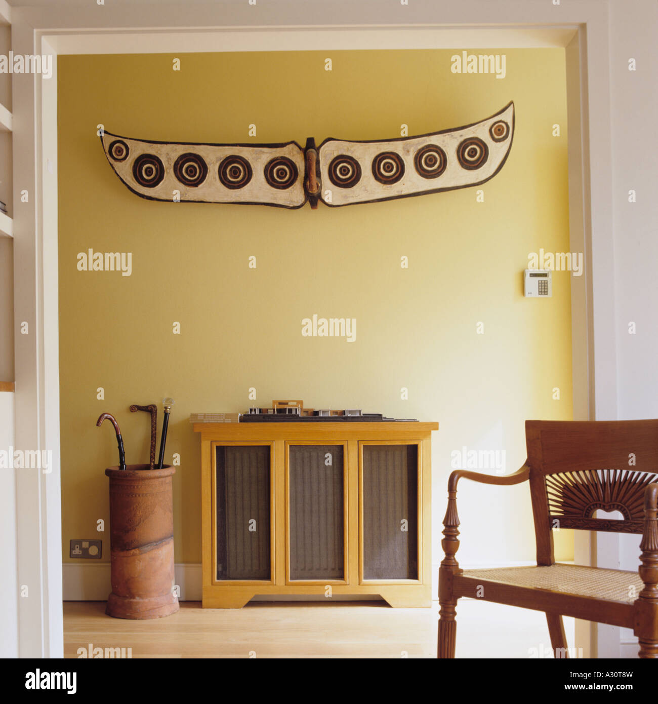 Yellow entrance hall with ethnic wall-piece and umbrella stand - Stock Image