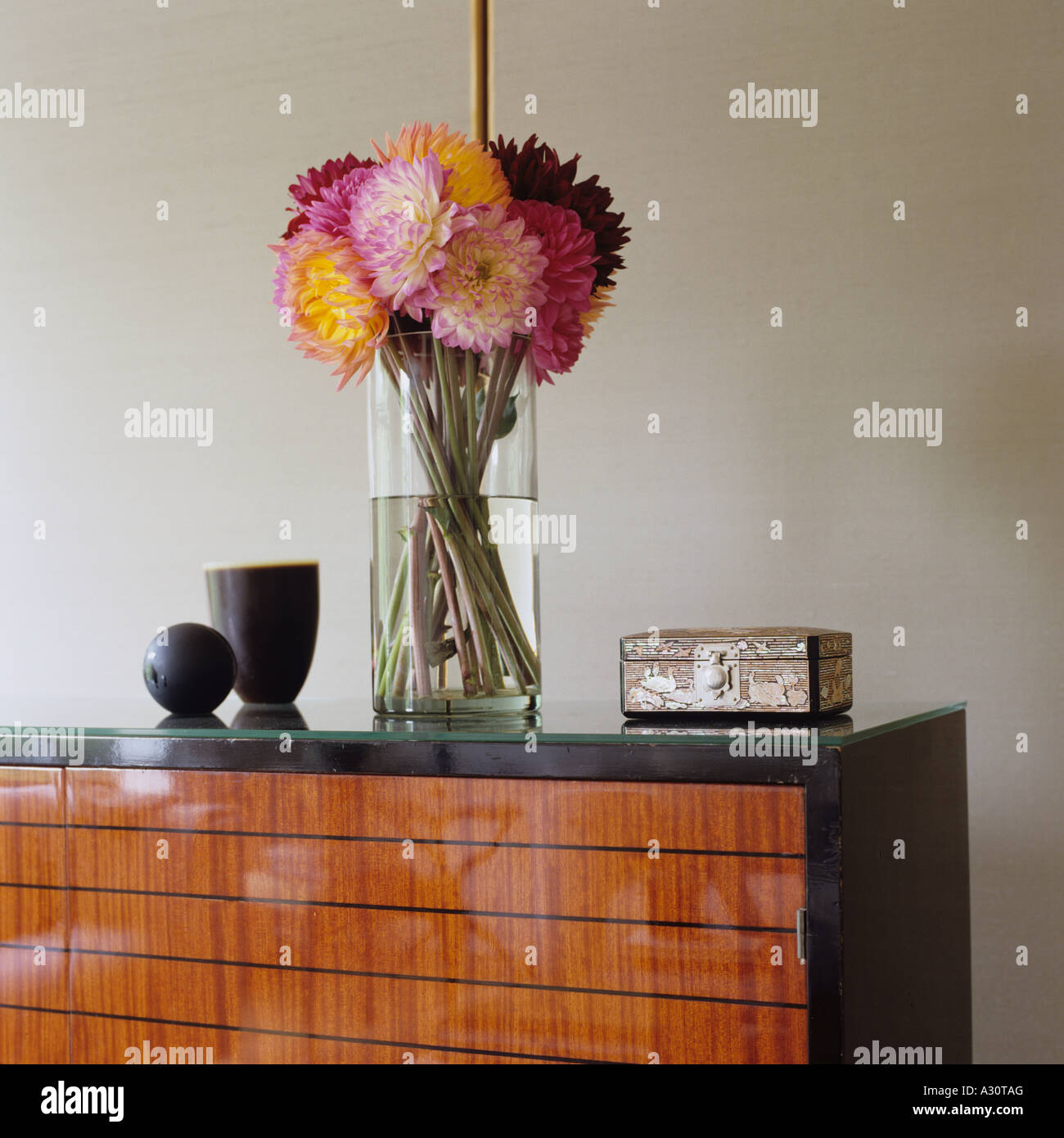 Vase of flowers on highly polished wooden sideboard - Stock Image
