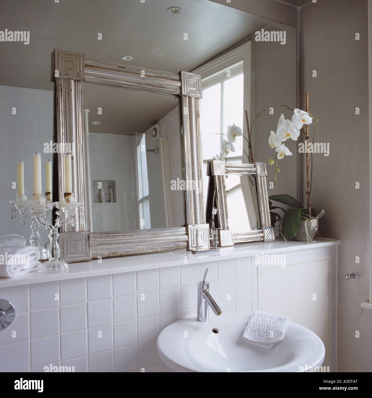 contemporary white bathroom with smaller framed mirrors leaning