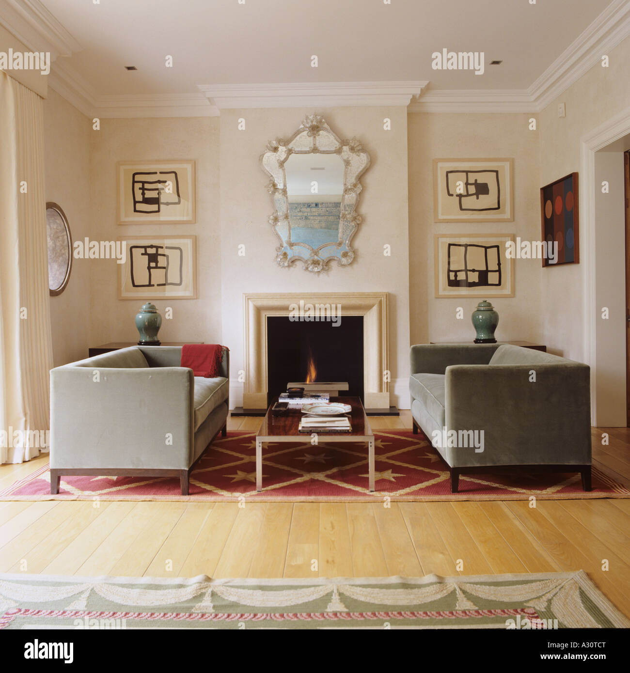 Fireplace in a London drawing room and symmetrically placed sofas - Stock Image