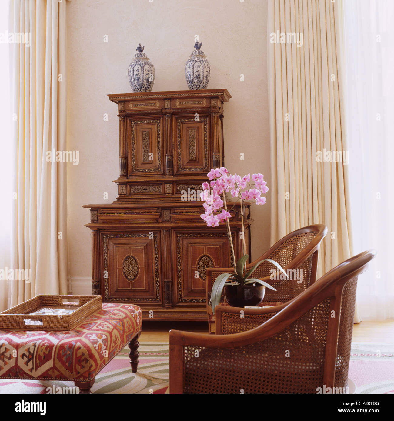 Antique sideboard in drawing room with wicker armchairs and a kilim covered ottoman - Stock Image