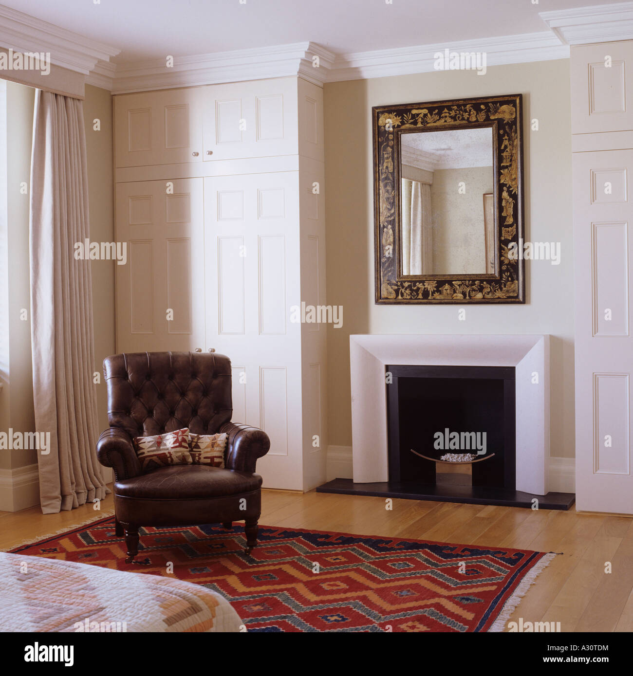 view of a fireplace and leather armchair in a bedroom - Stock Image