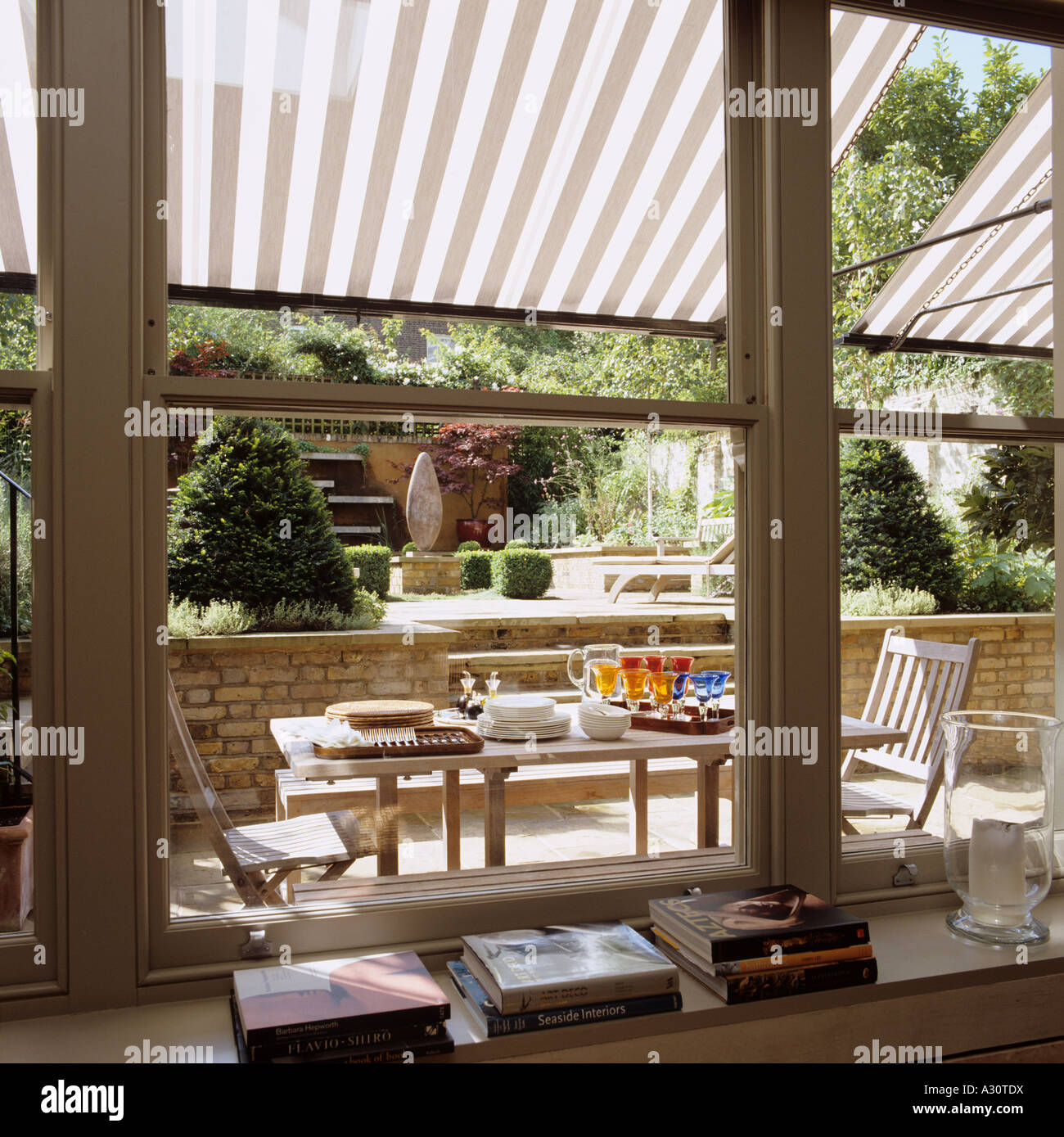 View Through Window To Garden Patio With Striped Awning