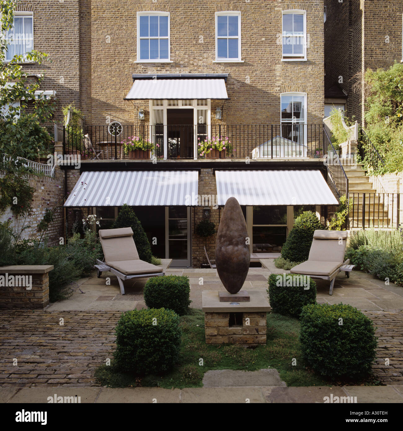 a modern garden of a London townhouse with awnings and sun loungers - Stock Image