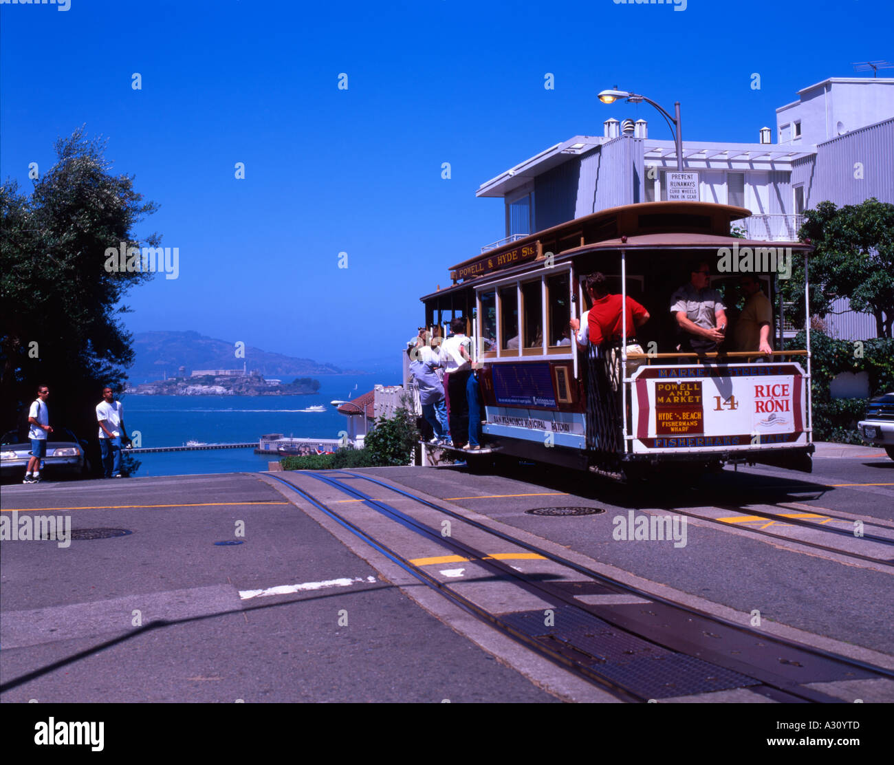 A San Francisco Cable Car Climbs A Steep Hill Overlooking