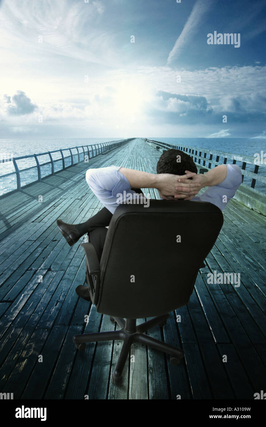 a business man relaxing in a chair whilst looking at the path ahead - Stock Image